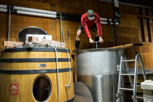 Aaron Pott, a winemaker and wine making consultant, works on pushing down grape skins that had risen to the top during the fermentation process of wine from his own label at Quixote Winery in Napa, Calif., on Friday, September 30, 2016. In addition to consulting there Pott shares space with the winery and produces his own label, Pott Wines, at the location.